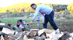 Man chopping wood with an ax while his children play in the yard Stock Footage