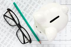 Stock Photo of Financial reports,glasses,pencil and piggy bank. Concept for economy and savi