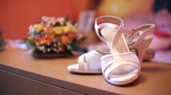 Bride's white shoes and a bouquet of flowers, placed on a nightstand Stock Footage