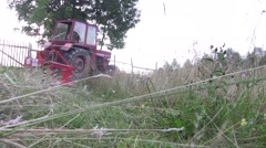 Tractor mowing high grass grown on land behind the house Stock Footage