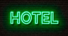 Neon sign on a brick wall - Hotel - stock photo