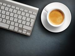 Coffee mug on the table with a keyboard - stock photo