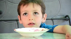 Early age boy sitting at the table next to empty plate and is glad that finished Stock Footage