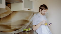 The man in kitchen uses phone and smiles Stock Footage