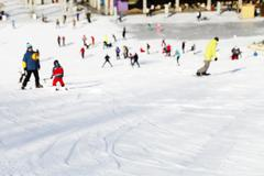Blurred Mass descent of mountain skiers and snowboarders - stock photo