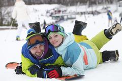 young couple snowboarders rejoice and be glad - stock photo
