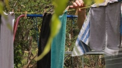 Man taking towels off of a line for drying Stock Footage