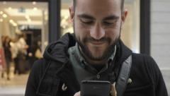 Young man using smartphone in public commercial street slomo crane up Stock Footage
