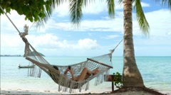Woman using mobile phone in a hammock on the beach - stock footage