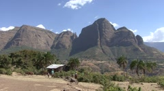 Cow herders with cows and villagers walking in front of scenic Simian Mountains Stock Footage