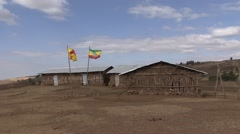 Ethiopian flags in front of traditional village school in Simien Mountains Stock Footage