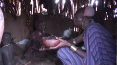 Hamer tribe men and child eat and talk and woman serves food inside hut Stock Footage