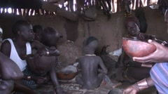 Hamer tribe men eat and talk with traditional dressed woman inside hut in Omo Stock Footage