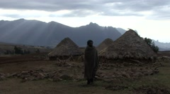 Simian Mountain tribal man walk in front of rondavel hut in the afternoon Stock Footage