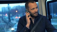 Young man talking on cellphone during tram ride Stock Footage