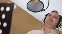 Portrait of man sing in headphones in front of microphone. Studio. Waggle Stock Footage