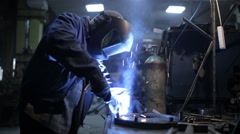 Welder in a protective helmet working on an industrial enterprise Stock Footage