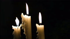 Close-up footage of three white tall and fired candles being blown  Stock Footage
