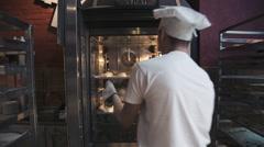 Baker lozhit bun in the oven - stock footage