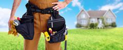 Builder handyman near new house. Stock Photos