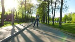 Young man run on inline skates along park path, sun shine through trees - stock footage