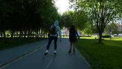 Young couple on roller skates, ride along park alley, from sunny to shaded area Stock Footage