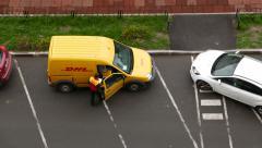 Unidentified courier stand inside open compartment door of yellow panel van Stock Footage