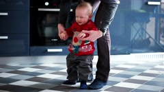 Baby boy walking his first step with his fathers help Stock Footage