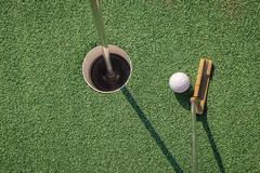 Putter with golf ball and hole - stock photo
