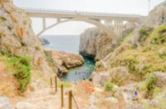 Defocused background of scenic seascape at Ciolo Bridge, Apulia, Italy - stock photo