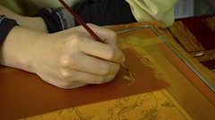 Cambodian Artist Hand Painting in Fine Detail in a Traditional Workshop. Stock Footage