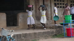 FEMALE STUDENTS CARRYING WATER BASINS ON THEIR HEADS WALK BY CLASSROOMS Stock Footage