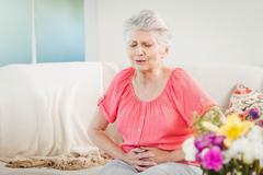 Senior woman suffering from stomach pain Stock Photos