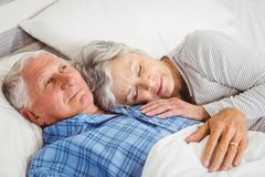 Stock Photo of Senior man lying awake next to asleep senior woman