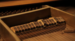 Inside vintage piano hammer hitting strings - stock footage