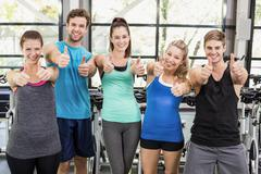 Athletic men and women posing with thumbs up - stock photo