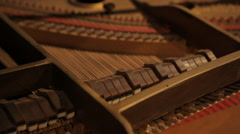 Close up of inside retro piano's hammers striking strings - stock footage
