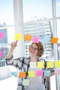 smiling hipster woman sticking notes on a notice board - stock photo