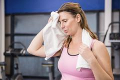 Tired pregnant woman wiping sweat with towel - stock photo