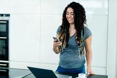 Woman standing near worktop with a mobile phone - stock photo