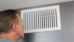 Man Looking in an Air Vent - stock footage