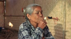 Burmese old woman smoking a big handmade cigar. Bagan, Myanmar, Burma - stock footage