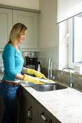 Stock Photo of Pretty blonde woman doing house chores