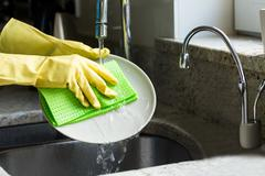 Pretty blonde woman doing house chores Stock Photos
