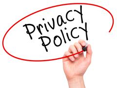 Man Hand writing Privacy Policy black marker on visual screen Stock Photos