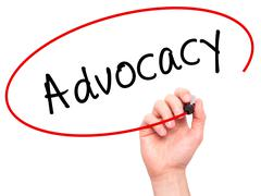 Man Hand writing Advocacy with marker on transparent wipe board - stock photo