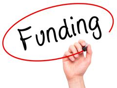 Man Hand writing Funding with marker on transparent wipe board - stock photo