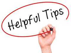 Man hand writing Helpful Tips on visual screen - stock photo