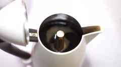 Detail of the coffee that comes out by a white coffee pot. - stock footage