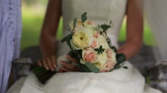 bride on a swing while holding a bouquet in hands - stock footage